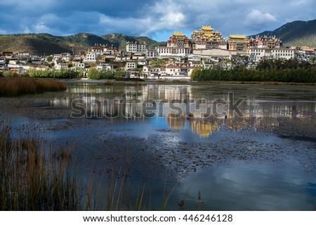 Songzanlin Monastery and the lake view foreground, Shangri-la County, Yunnan Province, China - stock photo