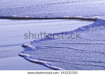 Soothing view of saltwater spreading across sandy beach shortly after sunrise in Cape Cod - stock photo