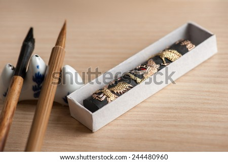 Sophisticated art of calligraphy. Closeup image of brushes and other tools for Japanese or Chinese calligraphy accurately prepared on wooden table - stock photo