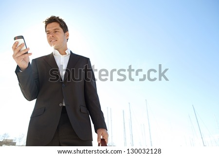 Sophisticated businessman standing on a marine with sailing boats around him, using a smart phone against a blue sky with the sun shining through. - stock photo