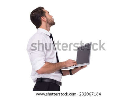 Sophisticated businessman standing using a laptop on white background