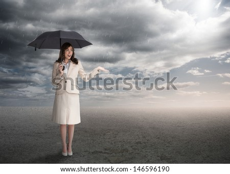 Sophisticated businesswoman holding an umbrella during stormy weather