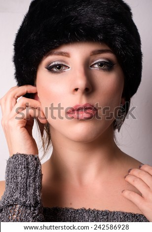 Sophisticated elegant young woman in elegant winter fashion wearing a fur hat and knitwear looking directly at the camera with her hand raised to her cheek - stock photo
