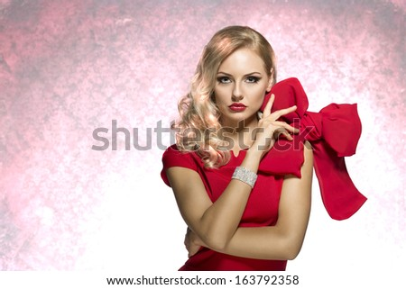 sophisticated lady in red dress with shining bracalet and elegant hair style looking in camera. keep the big bow - stock photo