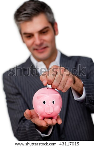 Sophisticated male executive saving money in a piggybank against a white background