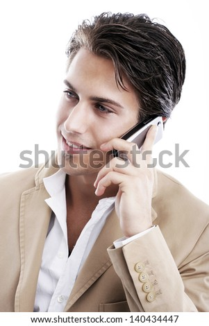 Sophisticated young man smiling while talking on the phone on a white background