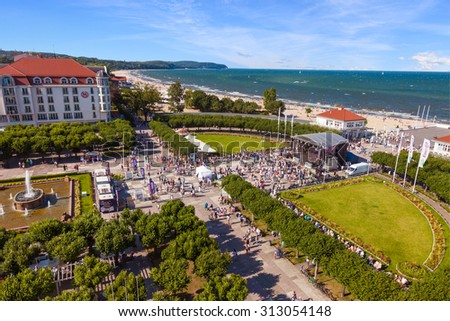 SOPOT, POLAND - AUGUST 09: Crowd of people walking on square near wooden pier in the distance, on August 09, 2015 in Sopot, Poland. Sopot is very popular tourist resort in Poland. - stock photo
