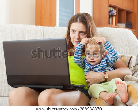 sorehead mother with  baby working online with laptop at home - stock photo