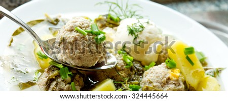 Sorrel soup with meatballs and eggs in a bowl. - stock photo