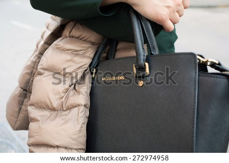 SORRENTO, ITALY - APRIL, 19, 2015: Close up of a Michael Kors bag while a young woman walking in the town center between fashion stores, Sorrento. - stock photo
