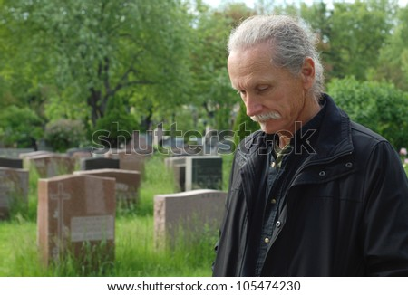 Sorrowful man standing in cemetery with head bowed - stock photo