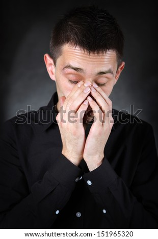 Sorrowful Young Man Portrait in the Black Shirt on The Dark Background - stock photo