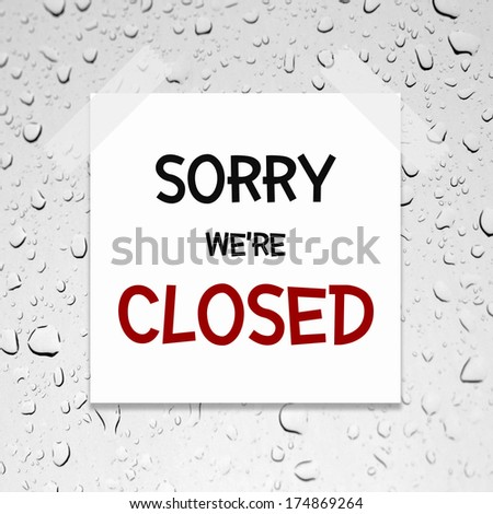 sorry we're closed written on piece of paper, on a glass with raindrops background. - stock photo