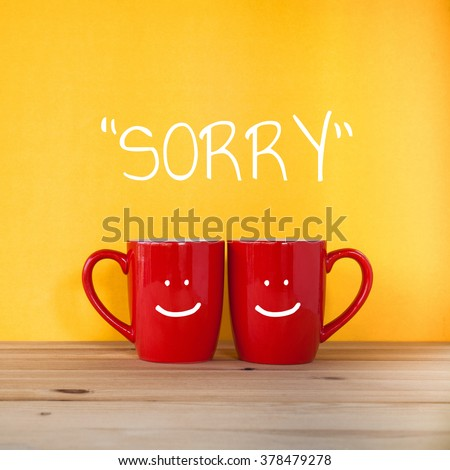 Sorry word.Two cups of coffee and stand together to be heart shape on yellow background with smile face on cup. - stock photo