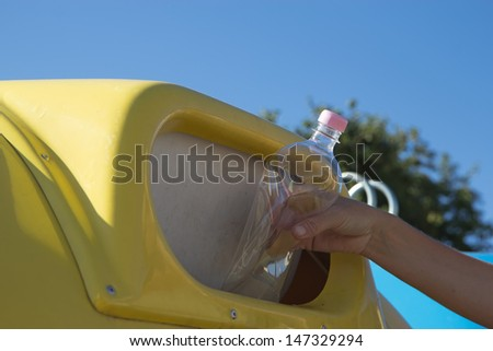 Sorting and recycling household waste. Hand throwing a plastic bottle in the trash. - stock photo
