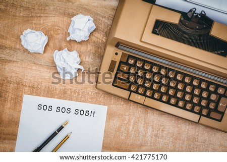 SOS message on a white background against view of an old typewriter