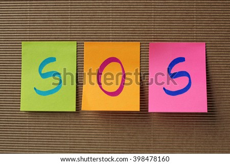 SOS text on colorful sticky notes - stock photo