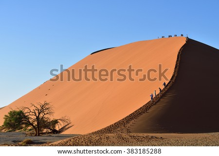 SOSSUSVLEI, NAMIBIA - JAN 29, 2016: Tourists climb Dune No.45 in a year that was declared as a drought year by the government in Namibia, Africa