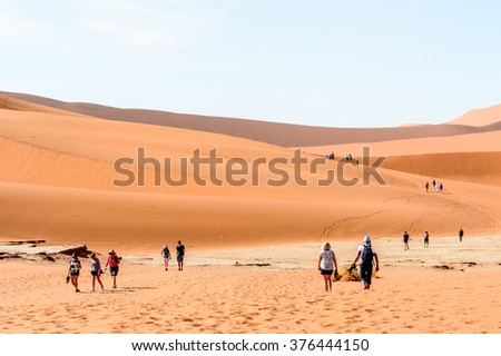 SOSSUVLEI, NAMIBIA - JAN 4, 2016: Unidentified people walk in Sossuvlei, which is one of the major visitor attractions of Namibia.
