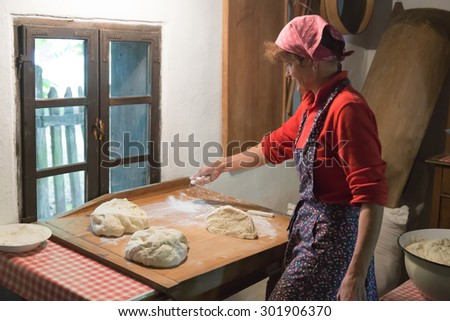 SOSTO, HUNGARY - CIRCA JUNE 2015 - Unidentified female baker preparing pastries in a rustic kitchen for a celebration at the Sosto Open Air Museum - stock photo