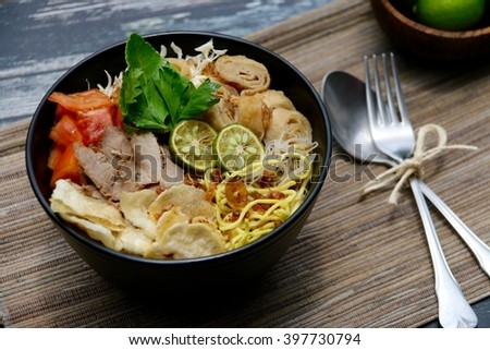 Soto Mie Bogor. Spicy beef noodle soup from Bogor, West Java. Typically street food, now served fancy style in black ceramic bowl. Lined with organic plant-fiber mat with a spoon and fork left aside. - stock photo