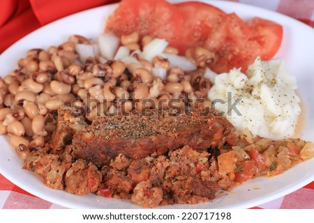 Soul food supper - meatloaf with black -eyed peas and mashed potatoes on red plaid tablecloth.  Closeup with selective focus. - stock photo