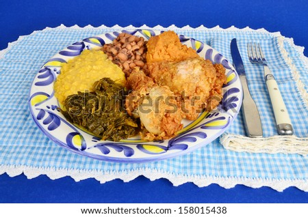 Soul food supper of fried chicken with collard greens; creamed corn; black eyed peas and candied yams on blue gingham background. - stock photo