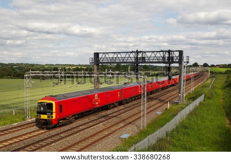 SOULBURY, UK - JUNE 15: A Royal Mail post train heads toward Crewe with an evening service on June 15, 2015 in Soulbury. There are currently 15, 325 post trainsets in use across the UK rail network.