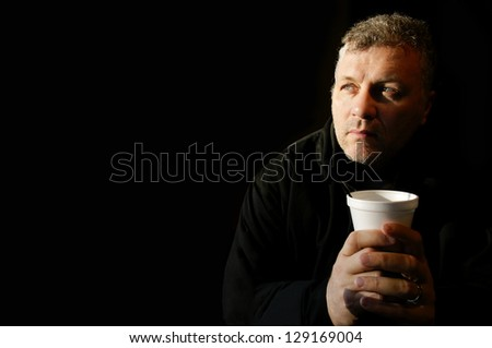 Soulful middle aged man holding a coffee cup with room for text on left side.