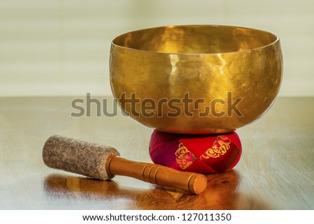 Sound bowl on a table with red bolster - stock photo