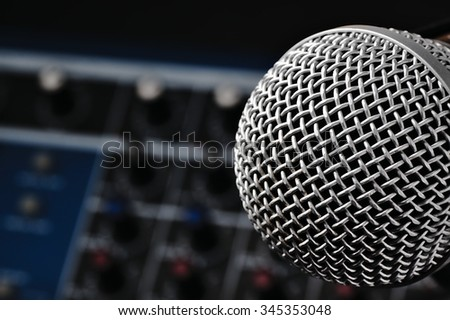 Sound console with buttons in the background and a dynamic microphone in the foreground.