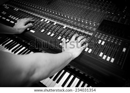 sound engineer hands on studio mixer & electric piano, synthesizer in home studio - stock photo