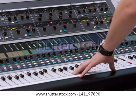 sound engineer's hand moving on sound mixing board - stock photo