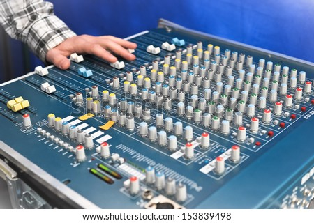 sound engineer's hand moving sliders on audio mixing board - stock photo