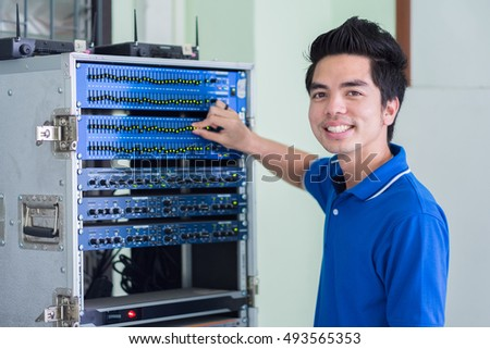 Sound engineer working at mixing panel in sound studio. Asian engineer.