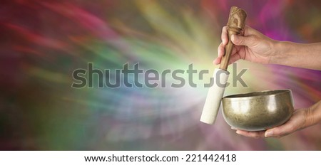Sound Healer's website banner  -  Sound healing practitioner with Tibetan Singing Bowl on a muted color background showing sound wave effects  - stock photo