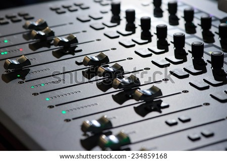 Sound mixer. Professional audio mixing console with lights, buttons, faders and sliders. - stock photo