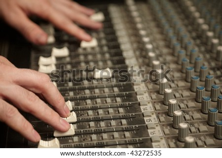 sound producer moving fads of dirty sound mixer panel. focus on fingers of right hand - stock photo