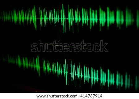 Sound waves oscillating green glow light.