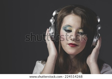 Sound, young girl listening music with huge headphones - stock photo