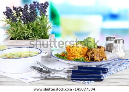 Soup and rice with meat in plates on napkins on wooden table on window background