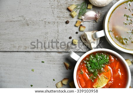 Soup bowls composition with text copy space mushroom cream soup fish and tomato in bowl with garlic parsley dill and croutons on rustic wood background - stock photo