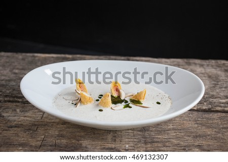 Soup for appetizer food on wooden table and black background.
