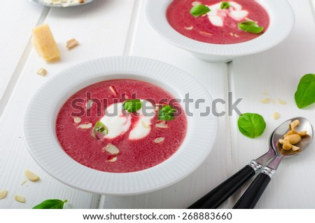 Soup from beet with light creame, nuts and basil sprinkled, organic beet - stock photo