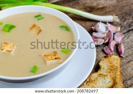 Soup garlic with toasted croutons on wood table