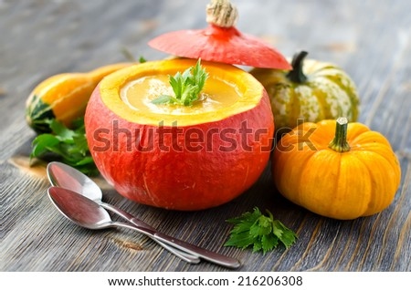 Soup in a pumpkin with different pumpkins for autumn dinner - stock photo