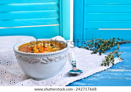 Soup of red lentils and vegetables in a ceramic plate - stock photo