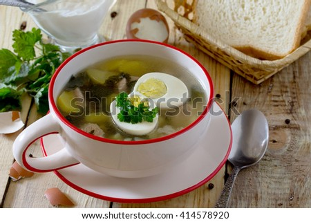 Soup of young nettle with eggs, selective focus. Space for your text. - stock photo