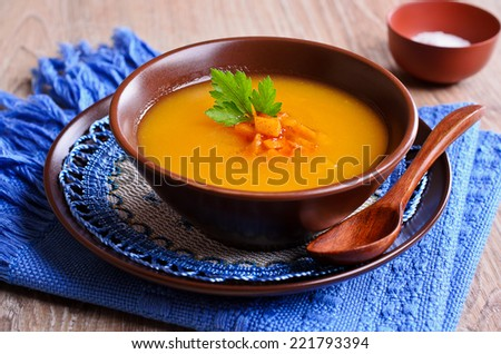 Soup orange color with chunks of roasted vegetables - stock photo