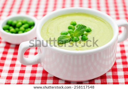 soup puree of green peas on a red white background. tinting. selective focus - stock photo